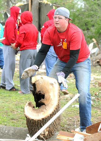 Baxter Springs first baseman Mason Williams rolls a large chunk of tree Tuesday as he joins teammates in clean up of Baxter Springs after an F-2 tornado struck the town on Sunday night.<br /> Globe | Laurie Sisk