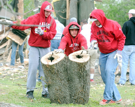 From the left: Baxter Springs High School baseball players Cody Rowe,  Dallas Hutchison and  Derek Barnes aid in the clean up effort on Tuesday after an F-2 tornado destroyed score of homes and business Sunday in Baxter Springs.<br /> Globe | Laurie Sisk