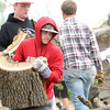 Baxter Springs baseball player Dallas Hutchison carries a large chunk of tree Tuesday as he joins teammates in clean up of Baxter Springs after an F-2 tornado struck the town on Sunday night.<br /> Globe | Laurie Sisk