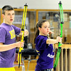 Sarcoxie archers Gavin Currey, left and Ariana Goddard watch their arrows land in the bullseye during archery practice on Wednesday at Sarcoxie High School.<br /> Globe | Laurie Sisk