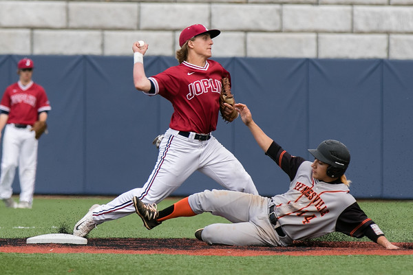 Globe/Israel Perez<br /> Joplin's infield Gavin Merriman (12) forces Waynesville's Noah Ochoa (14) out on second base and throws to first base for a double play during Thursday's game  at the JHS field.