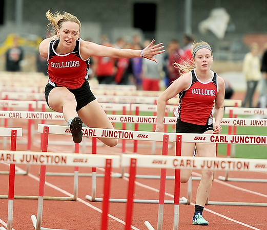 Carl Junction's Lexi Miller, left and Gracie Smith capture first and second place respectively in their heat of the hurdles on Friday at CJHS.<br /> Globe | Laurie Sisk