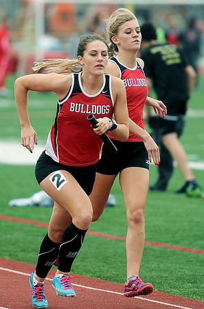 Carl Junction's Jordyn Capra, right, hands the baton off to anchor JeLynn Tatum as the Lady Bulldogs capture first place in the 4x800 relay on Friday at CJHS.<br /> Globe | Laurie Sisk