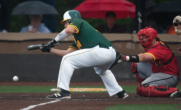 Missouri Southern's Brian Prost lays down a scarifice bunt during the Lions game against Pittsburg State on Wednesday night at Warren Turner Field. Also pictured is PSU catcher TJ Martin.<br /> Globe | Laurie Sisk