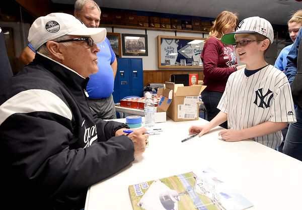 Former Yankee great Bucky Dent signs a baseball card for Yankee fan Jonathan Myers, 10, of Green River, Wyo. on Saturday at Commerce High School as the guest celebrity for the Mickey Mantle Classic. Myers and his family traveled to the tournament to check out historic sites related to Mickey Mantle and attend the events surrounding the annual tournament.<br /> Globe | Laurie Sisk