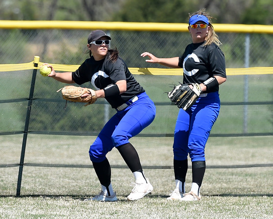 Crowder leftfielder Daryan Torix retrieves a ball at the base of the fence as teammate Lexi McClellan looks on during the Roughriders opening game of the Region XVI NJCAA Championship against State Fair on Friday morning at the Joplin Athletic Complex.<br /> Globe | Laurie Sisk