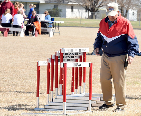 Longtime track official Oscar Birk helps clear hurdles during a track meet last Thursday at Northeast in Arma. Birk has interacted with an estimated 250,000 athletes during his 37-year career.<br /> Globe   Laurie Sisk