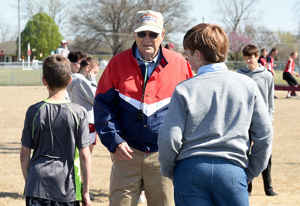 Longtime track official Oscar Birk chats with junior high school athletes during a track meet last Thursday at Northeast in Arma. Birk has interacted with an estimated 250,000 athletes during his 37-year career.<br /> Globe | Laurie Sisk