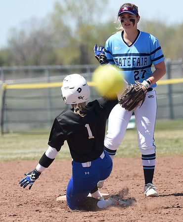 Crowder's Kenzi Spurgin advances to second base as a hit ball makes its way into the outfield during the Roughriders opening game of the Region XVI NJCAA Championship on Friday morning at the Joplin Athletic Complex. Looking on is State Fair infielder Kylie Johnson.<br /> Globe | Laurie Sisk