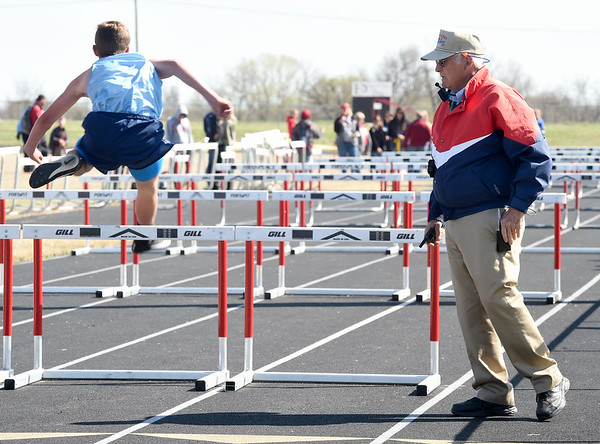 Longtime track official Oscar Birk watches as junior high school athletes compete in the hurdles during a track meet last Thursday at Northeast in Arma. Birk has interacted with an estimated 250,000 athletes during his 37-year career.<br /> Globe   Laurie Sisk