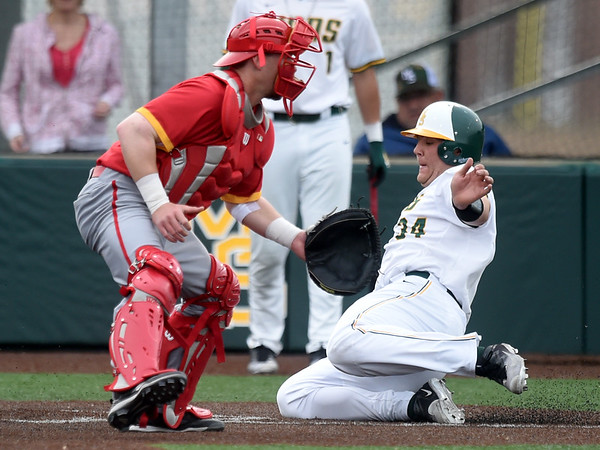 Missouri Southern's Alex Phillips slides home as Pittsburg State catcher Josh Whisler waits for the throw during their game on Wednesday night at Warren Turner Field.<br /> Globe   Laurie Sisk