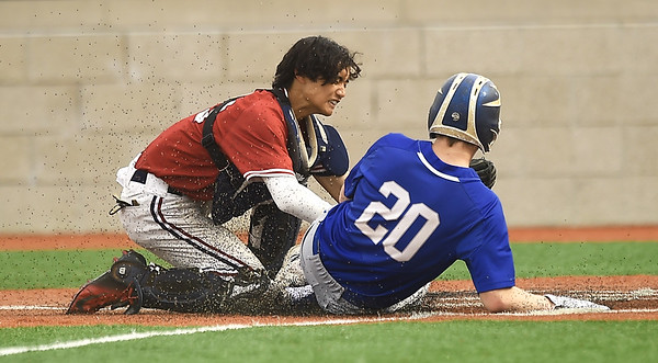 Joplin catcher Luke Benfield, left, tags out Carthage's Bryce Pugh (20) during their game on Tuesday at JHS. Globe | Laurie Sisk