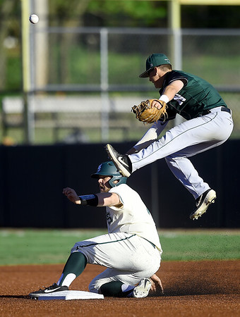 Missouri Southern's Alex Phillips slides safely into second base as Northeastern State's Jaxson Phipps leaps for an errant throw during their game on Friday night at Joe Becker Stadium.<br /> Globe | Laurie Sisk
