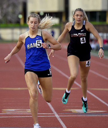 Riverton's Matti Price, left,  races to a second place finish in the 400m during the Gorilla Relays on Friday at Pittsburg State's Carnie Smith Stadium. Also pictured is Owasso's Sierra Williams. <br /> Globe | Laurie Sisk