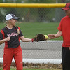 Jay Johnson, Liberal softball assistant coach, helps Brooke Bearden warm up before Monday's game at Liberal.<br /> Globe | Roger Nomer