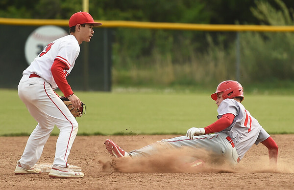 Webb City's Jacob Monroe (11) slides safely into second base as Carl Junction's Drew Beyer (15) awaits the throw during their game on Tuesday at Carl Junction.<br /> Globe   Laurie Sisk