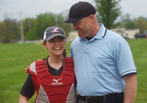 Brooke Bearden chats with umpire Brandon Smith before Monday's game in Liberal.<br /> Globe   Roger Nomer