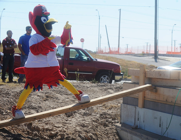 Globe/Roger Nomer<br /> Fred Bird gets hung up as he attempts to climb to the foundation of a Habitat for Humanity house during Monday's build.