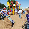 Globe/T. Rob Brown<br /> Kenny Marrs, left, of Liberty, a Red Coater volunteer with the Chiefs, dumps a wheelbarrow full of wood chips onto the new playground surface under the direction of Greg Perez, right, of Diamond, and a manager with C.K. Construction, Thursday afternoon, Aug. 23, 2012, at Beacon School, the former Joplin School District administration offices. Administration and personnel for the Kansas City Chiefs helped build the new playground alongside Joplin School District personnel and volunteers.