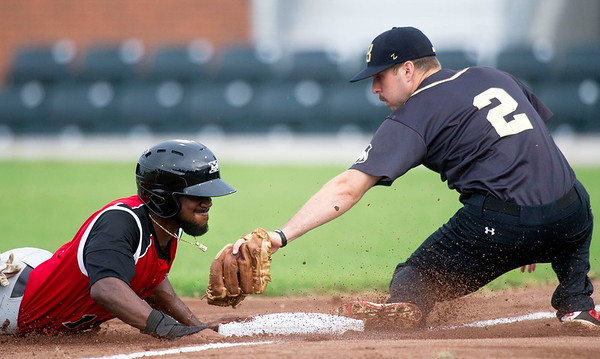 Sioux City's Derrick Robinson slides under the tag of Blasters third baseman Brandon Tierney during their game on Tuesday night at Joe Becker Stadium.<br /> Globe | Laurie Sisk