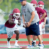 Joplin Assistant Coach Brad Cox works with runningback Dustin Hunter during the first practice of the season on Monday at JHS.<br /> Globe | Laurie Sisk
