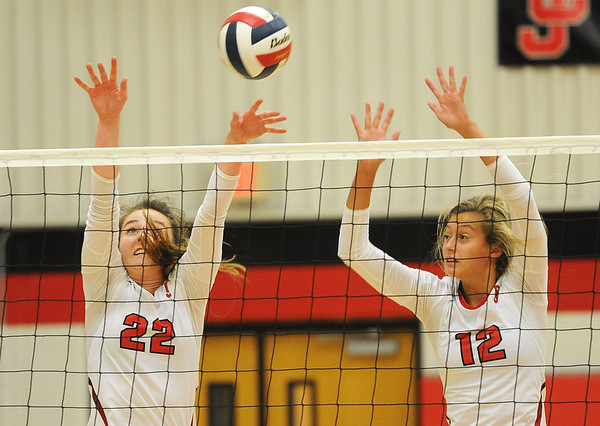 Carl Junction's Sylvia Lawson (22) and Olivia Lewis (12) try to block a spike by Joplin's Jillian Lopes during their match on Tuesday night against Carl Junction at CJHS.<br /> Globe   Laurie Sisk