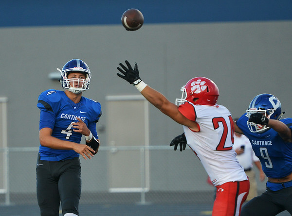 Globe/Roger Nomer<br /> Carthage's Zeke Sappington makes a pass over Ozark's Ethan Sandoval during Friday's game at David Haffner Stadium in Carthage.