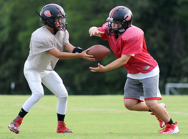 Quarterback Jack Roberts hands off to runningback Garrett Severs during practice for the Cornerstone Spartans on Thursday night.<br /> Globe | Laurie Sisk