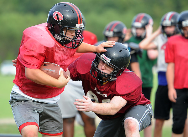 From the left: Runningback Garrett Severs tries to get past Brodie Hebert during practice for the Cornerstone Spartans on Thursday night.<br /> Globe | Laurie Sisk