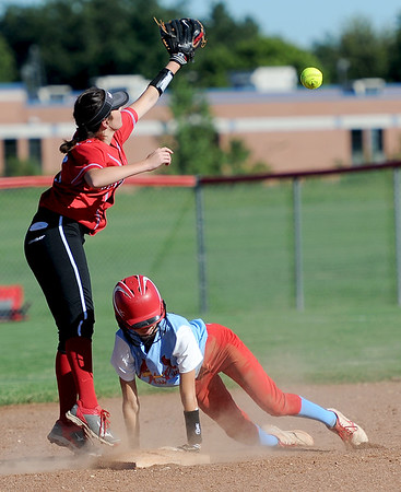 Webb City's Kaylee Cristy advances to second base on an error after reaching first on a single during the Cardinals' game against Carl Junction on Wednesday night at Webb City. Fielding the throw is Carl Junction shortstop Madison Bowers.<br /> Globe | Laurie Sisk