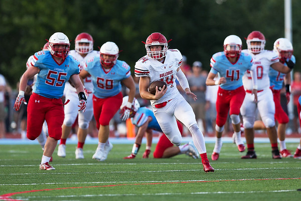 Globe|Israel Perez<br /> Carl Junction's Cade Beason (14) runs the ball through the middle of the field getting past the defensive line of Webb City during their season opener game on Friday night at Cardinal Stadium in Webb City.