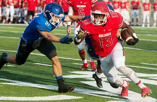 Globe/Roger Nomer<br /> Carl Junction's Rayquion Weston spins away from Carthage's Caden Browning during Friday's jamboree at David Haffner Stadium in Carthage.