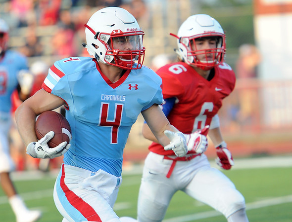 Webb City runningback Will Larson (4) runs the first play from scrimmage into the endzone as Seneca's Dawson Stephens defends during their scrimmage on Friday night at the Webb City - Seneca- Joplin Jamboree at Webb City.<br /> Globe | Laurie Sisk