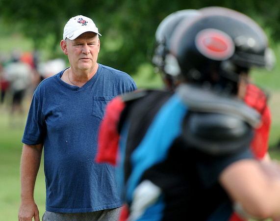 Defensive coordinator Scott Black works with his players during practice for the Cornerstone Spartans on Thursday night.<br /> Globe | Laurie Sisk