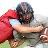 From the left: Noah Adcock works to stop quarterback Jack Roberts during practice for the Cornerstone Spartans on Thursday night.<br /> Globe | Laurie Sisk
