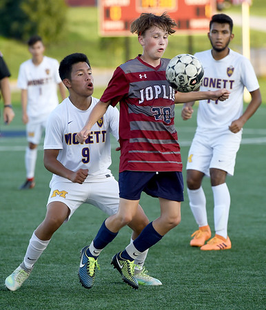 Joplin's Connor Simon (20) and Monett's Esvin Merida (9) battle for the ball during their match on Tuesday night at JHS.<br /> Globe | Laurie Sisk