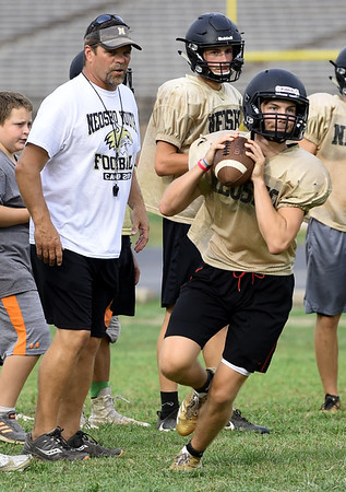 Neosho Head Coach Leon Miller looks on as quarterback Quincy Willis runs passing drills during practice on Friday at NHS.<br /> Globe | Laurie Sisk