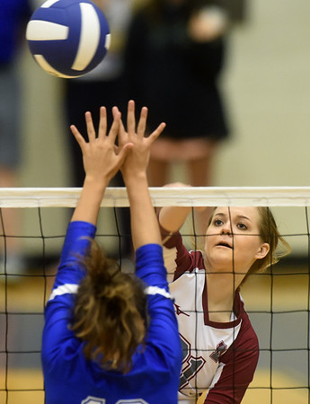 Nevada's Adrian Bond gets a spike over the outstretched arms of Carthage's Gracie Fagg during the Carthage Volleyball Jamboree on Tuesday night at Carthage High School.<br /> Globe | Laurie Sisk