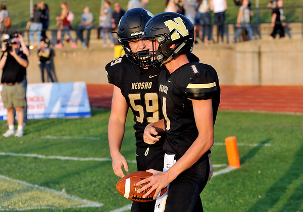 Neosho (1) and Sean Moran (59) celebrate after a touchdown against Ozark on Friday at Neosho.<br /> Globe | Willie Brown