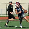 Joplin quarterback Blake Tash scrambles as assistant coach Brandon Taute pursues during the first day of football practice on Monday morning at JHS.<br /> Globe | Laurie Sisk