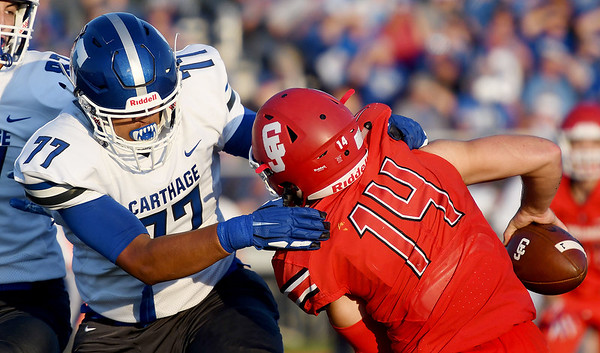 Carthage defensive end Oscar Campa (77) brings down Carl Junction quarterback Joe Kennedy (14) during their game on Friday night at Carl Junction.<br /> Globe | Laurie Sisk