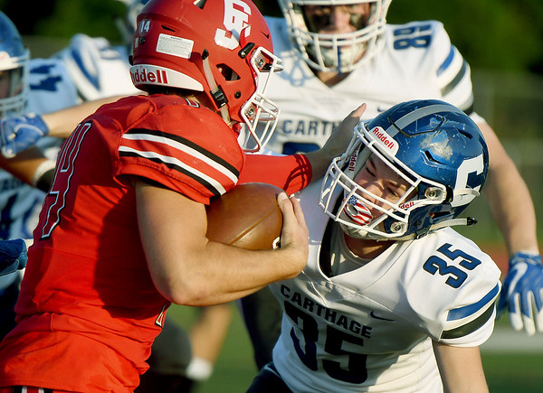 Carl Junction quarterback Joe Kennedy (14) tries to get past Carthage defensive back Bryce Pugh (35) during their game on Friday night at Carl Junction.<br /> Globe   Laurie Sisk