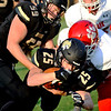 Neosho's Sean Moran (59) tries to keep teammate Cade Lyeria (25) from falling with the ball during Friday's game against Ozark in Neosho.<br /> Globe | Willie Brown
