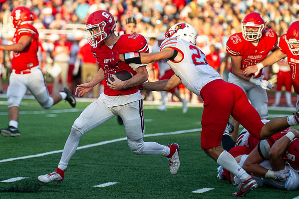 Carl Junction's Garret Taylor heads to the outside for some yards as Webb City's Ethan Trueblood(23) attempts to make the stop in Friday nights game in Carl Junction, Mo.
