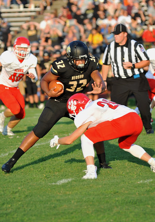 Neosho's Drayke Perry (32) is tackled by Ozark's Keaton Carson (28) during Friday's game in Neosho.<br /> Globe   Willie Brown