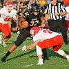 Neosho's Drayke Perry (32) is tackled by Ozark's Keaton Carson (28) during Friday's game in Neosho.<br /> Globe | Willie Brown