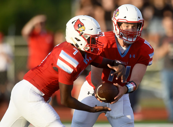 Webb City quarterback Cade Beason (14) hands off to runningback Durand Henderson (7) during their season opener against Carl Junction on Friday night at Webb City.<br /> Globe | Laurie Sisk