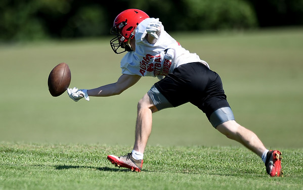 Aurora running back Brody Sims stretches for a pitch during practice on Wednesday at Aurora High School.<br /> Globe   Laurie Sisk