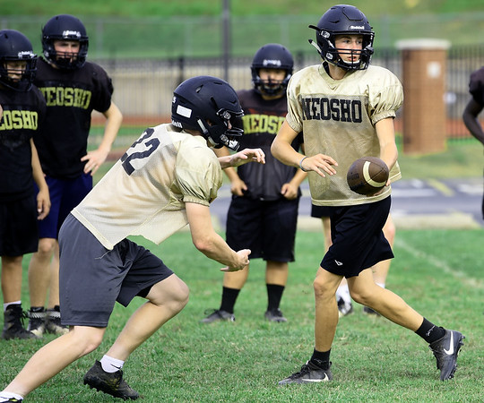 Neosho quarterback Gage Kelley hands off to runningback Cade Lyerla during practice on Friday at NHS.<br /> Globe | Laurie Sisk