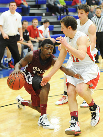 Globe/T. Rob Brown<br /> Joplin's Charlie Brown attempts to drive the ball around Carl Junction's J. Thomas during Saturday afternoon's championship game, Dec. 1, 2012, at Carthage High School's gymnasium.